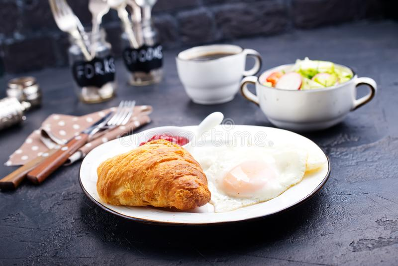 Breakfast. On a table, fried eggs and croissant royalty free stock photos