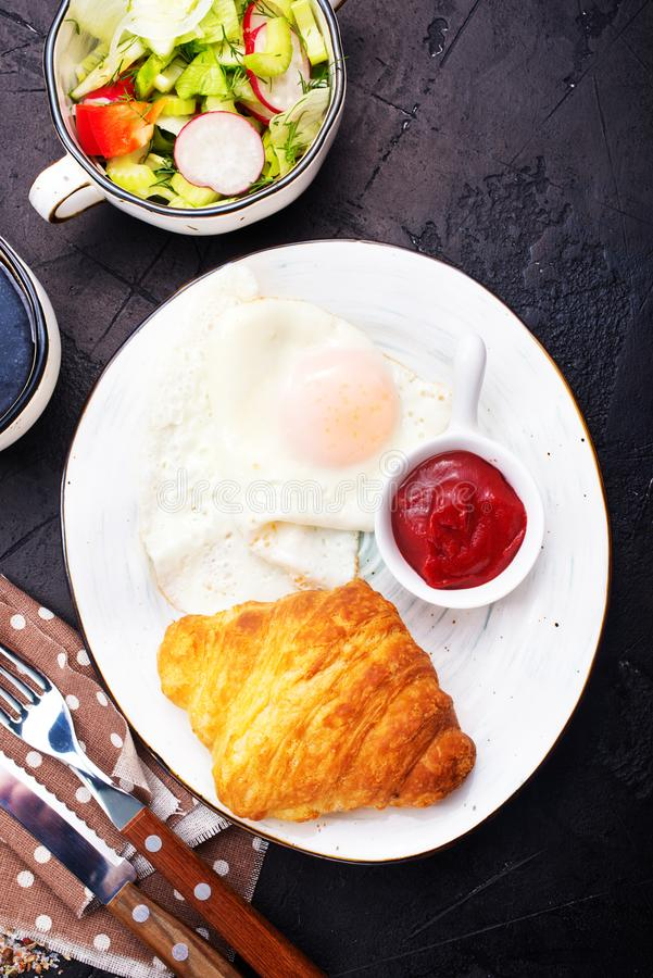 Breakfast. On a table, fried eggs and croissant stock photos