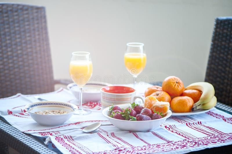 Breakfast on the table, juice, cereal and fruits in the sun. Goo. D food, proper breakfast, strawberries, tangerines, bananas, nuts stock images