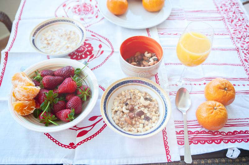 Breakfast on the table, juice, cereal and fruits in the sun. Goo. D food, proper breakfast, strawberries, tangerines, bananas, nuts royalty free stock images