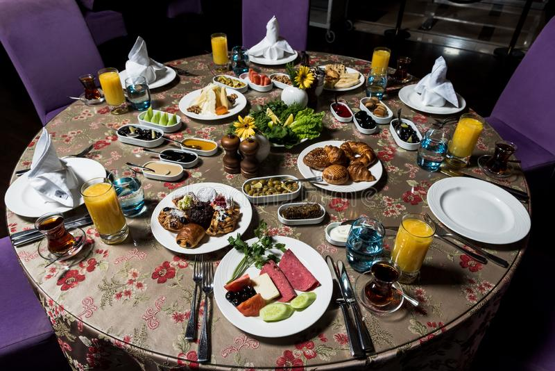 Breakfast table. Luxury and rich foods like patties, salamies and orange juices royalty free stock image