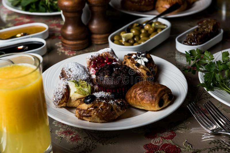 Breakfast table. Luxury and rich foods like salamies. Cakes and also some desserts stock photography