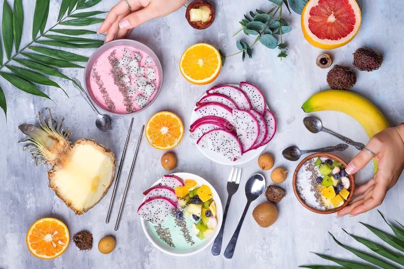 Breakfast table with yogurt acai bowls and fresh tropic fruits on a gray stone background with wooman hand and palm royalty free stock photo