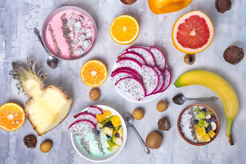 Breakfast table with yogurt strawberry smoothie bowls and fresh tropic fruits on a gray stone background. Acai bowl of royalty free stock photo