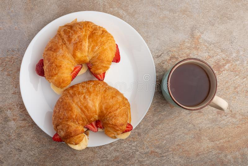 Breakfast with tea, croissant, bananas and strawberries. Top view, flat lay stock photography