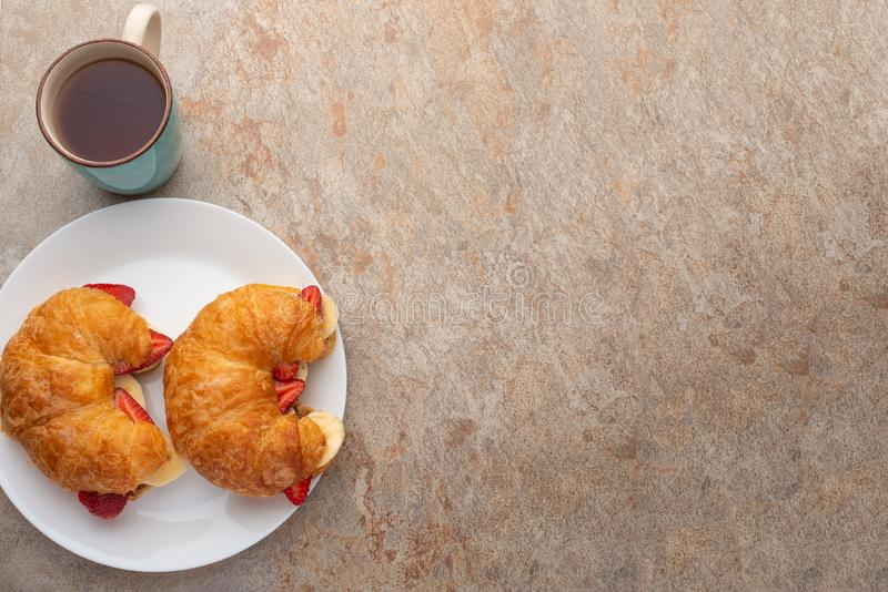 Breakfast with tea, croissant, bananas and strawberries. Top view, flat lay stock photo