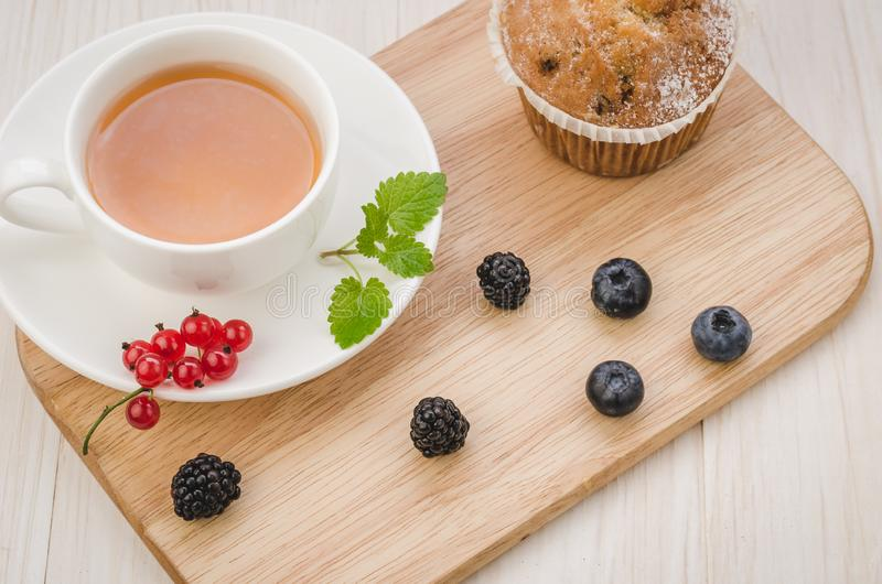 Breakfast: tea with mint, cake and fresh berries/healthy breakfast: tea with mint,  cake and fresh berries on a wooden surface. Top view cup brunch food stock photography