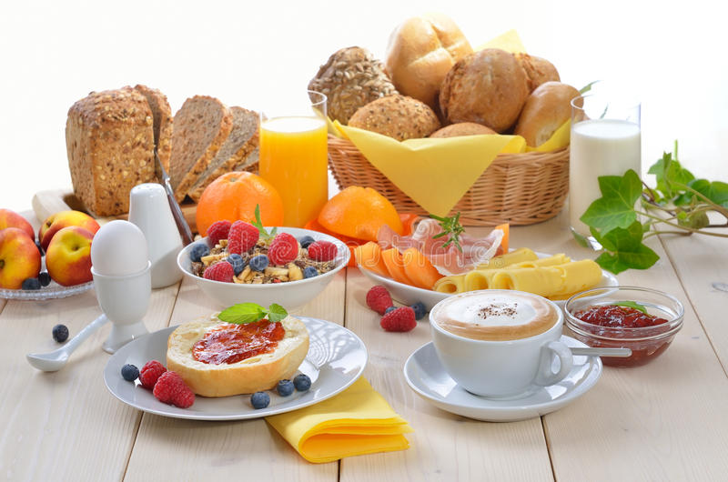 Breakfast time. Colorful breakfast with cappuccino, fruit, fresh orange juice, ham, cheese, fresh rolls and wholemeal bread royalty free stock photo