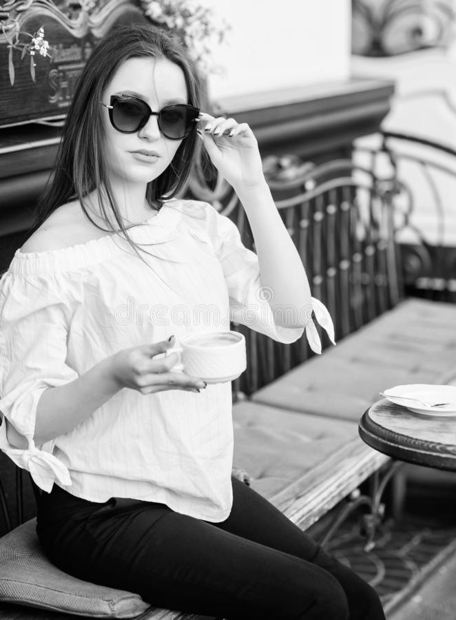 Breakfast time in cafe. Girl enjoy morning coffee. Woman in sunglasses drink coffee outdoors. Girl relax in cafe stock photos