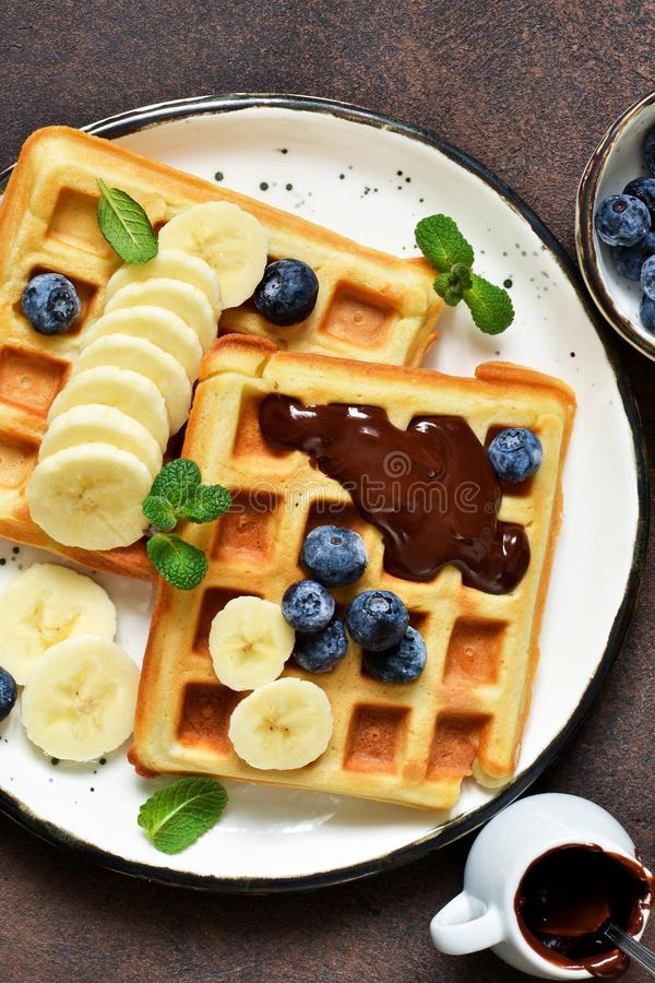 Breakfast time. Homemade waffles with banana, blueberry and chocolate spread on a kitchen table stock image