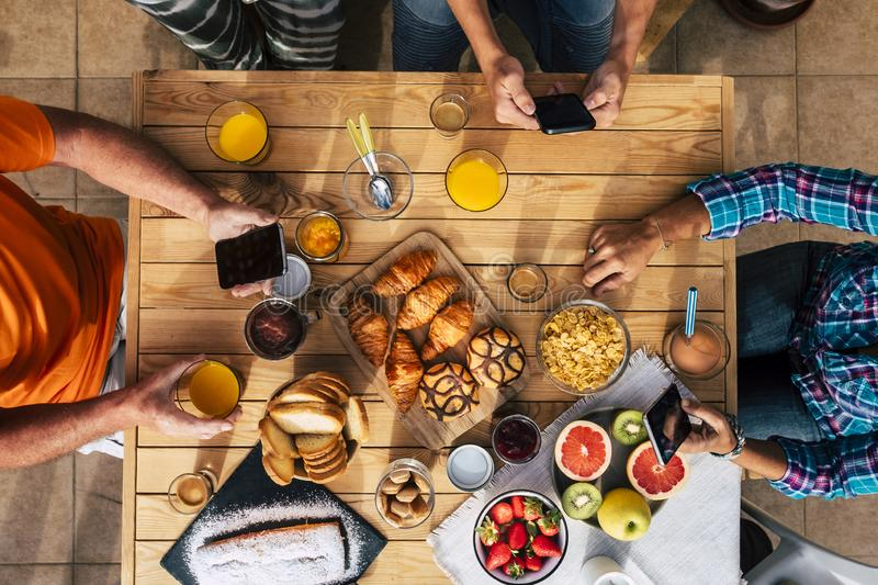 Breakfast time in vertical top view with family of friends eating together - technology mobile internet social network addiction stock image