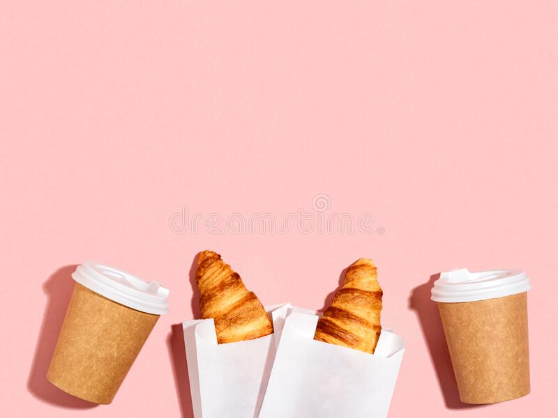 Breakfast to go with croissants and coffee. Takeaway breakfast for friends. Two paper cups and croissants on a pink background. Urban lifestyle. Top view, copy royalty free stock photos