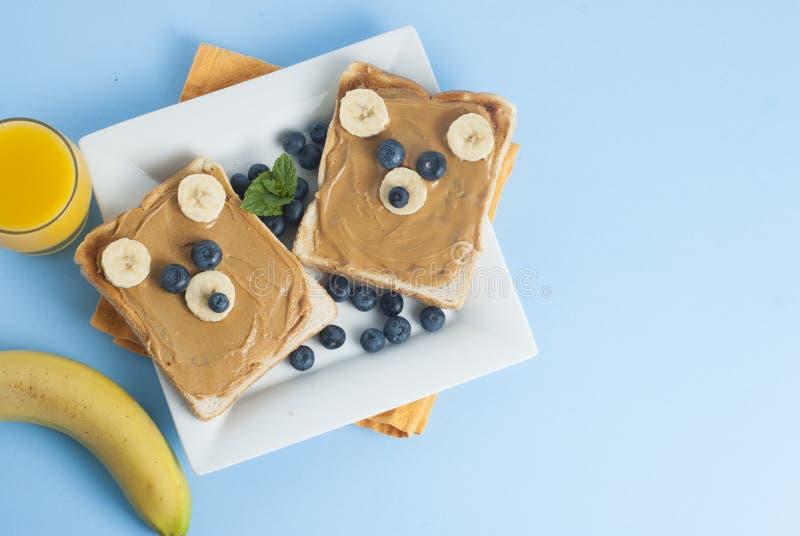 Breakfast Toast Bear Shaped Peanut Butter Banana Bread Blueberry for Kids. Funny animal face toast for kids snack. Blue Background. Breakfast Toast Bear Shaped royalty free stock image