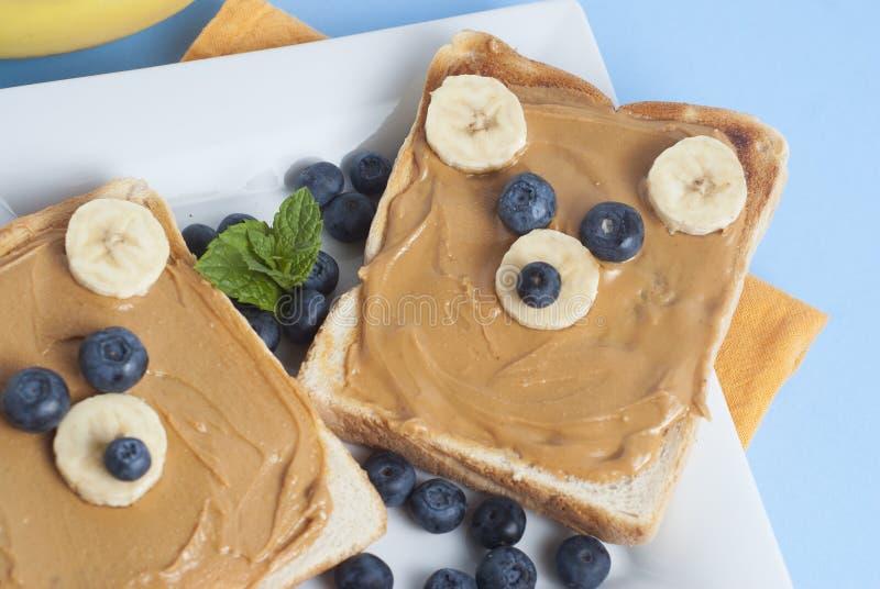 Breakfast Toast Bear Shaped Peanut Butter Banana Bread Blueberry for Kids. Funny animal face toast for kids snack. Blue Background. Breakfast Toast Bear Shaped stock photo