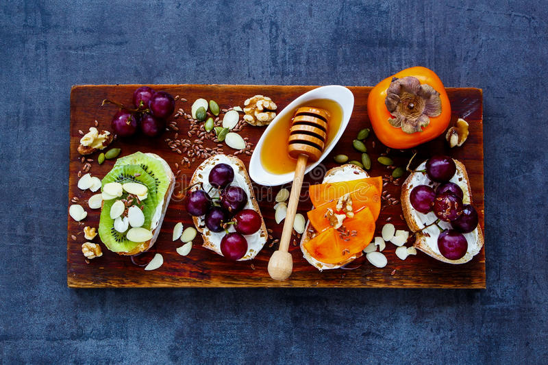 Breakfast toast pieces. Delicious toast pieces set. Wholegrain baguette slices with cream cheese, various fruit, honey, seeds and nuts for breakfast. Slate royalty free stock photography