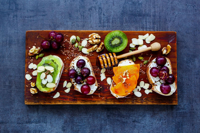 Breakfast toast pieces. Sweet toast pieces set for breakfast. Wholegrain baguette slices with cream cheese, various fruit, honey, seeds and nuts. Slate stock photos