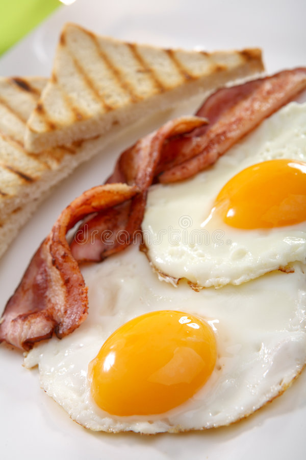 Breakfast - toasts, eggs, bacon. Breakfast concept - toasts, eggs, bacon royalty free stock image