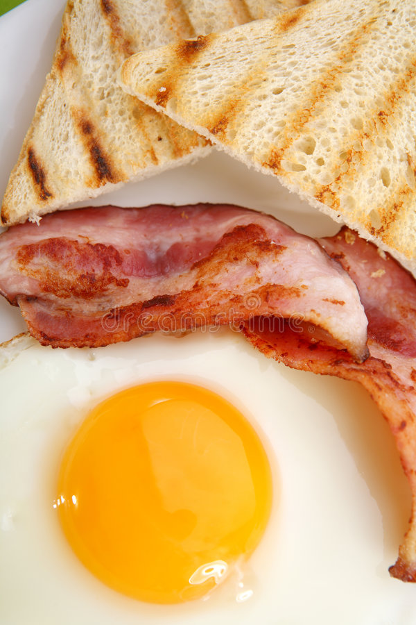 Breakfast - toasts, eggs, bacon. Breakfast concept - toasts, eggs, bacon royalty free stock photography