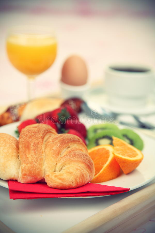 Breakfast tray. Continental breakfast. Breakfast tray on bed with coffee, orange juice, croissant, strawberries, kiwi, bread and egg. Shallow depth of field royalty free stock images