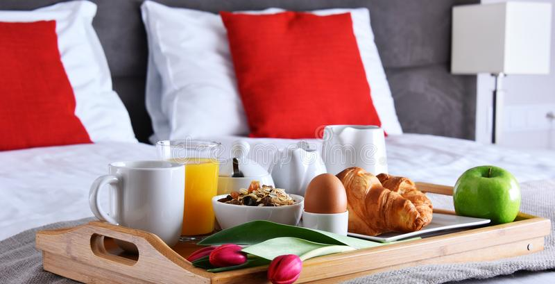 Breakfast on tray in bed in hotel room royalty free stock photography