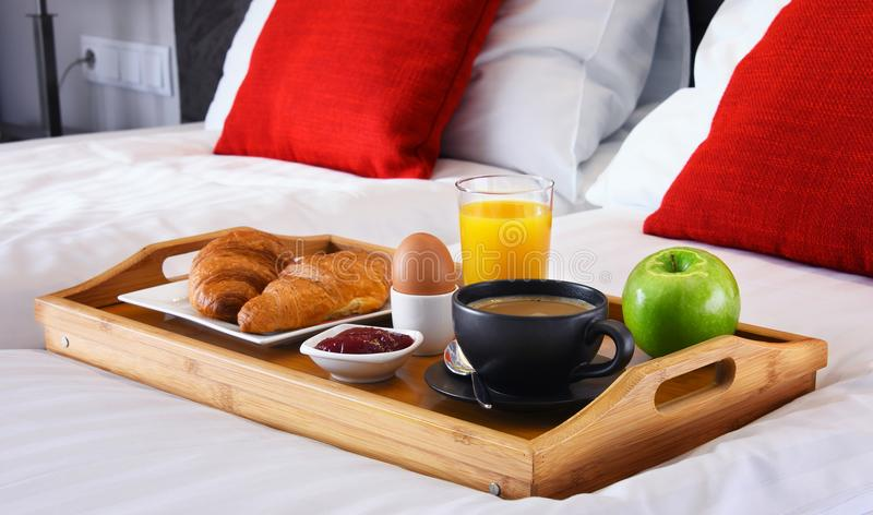 Breakfast on tray in bed in hotel room stock photo