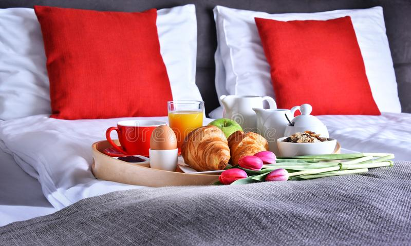 Breakfast on tray in bed in hotel room royalty free stock images