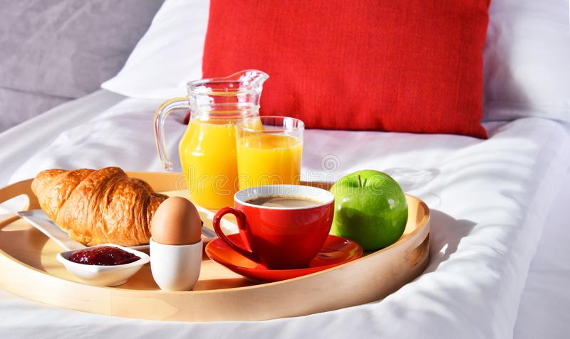 Breakfast on tray in bed in hotel room royalty free stock image