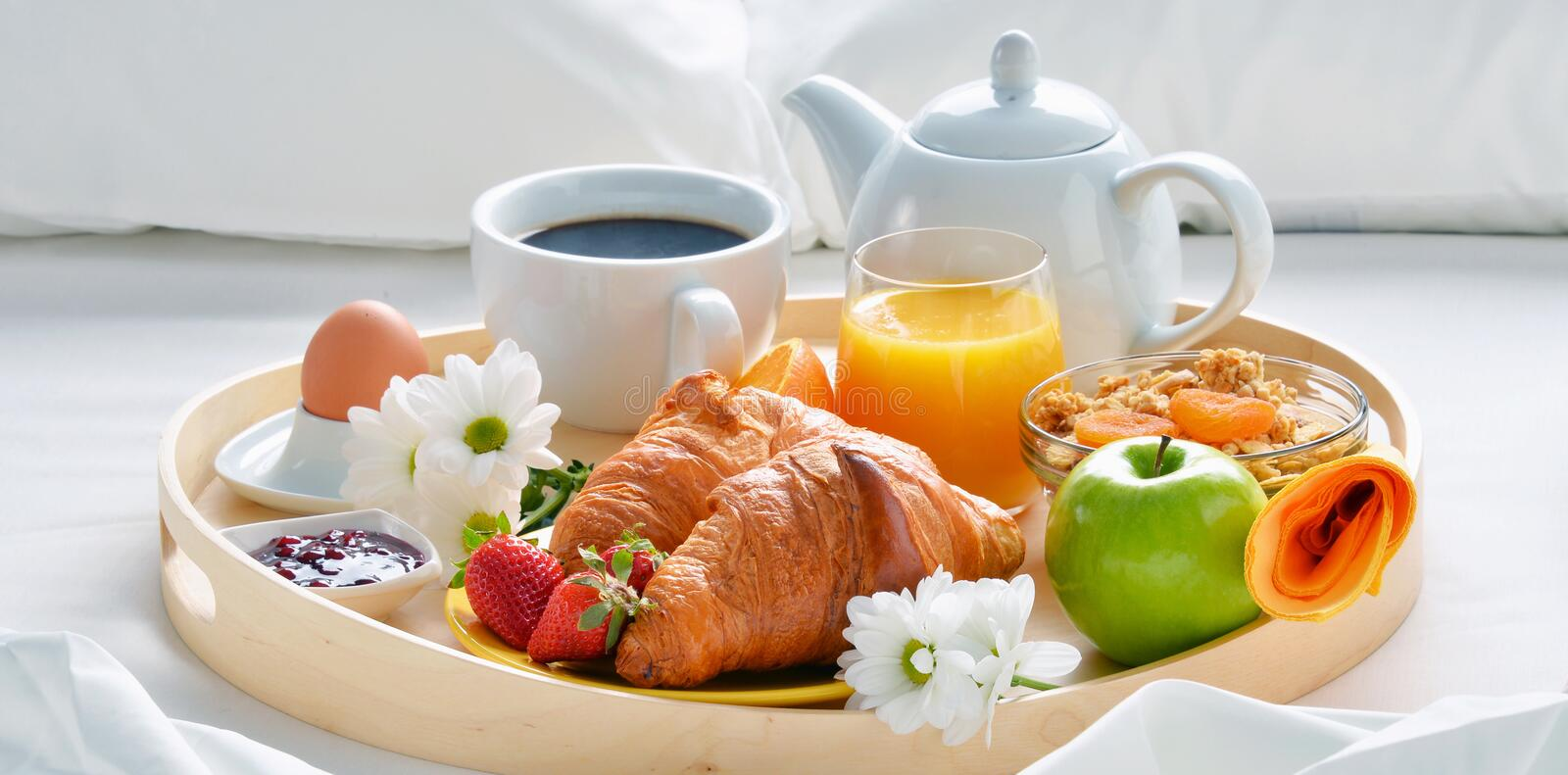 Breakfast tray in bed in hotel room royalty free stock photo
