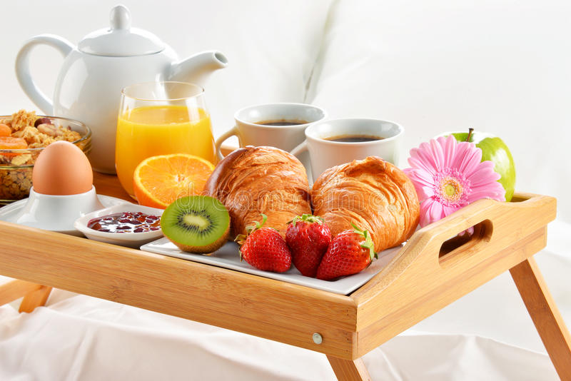 Breakfast tray in bed in hotel room.  stock photography