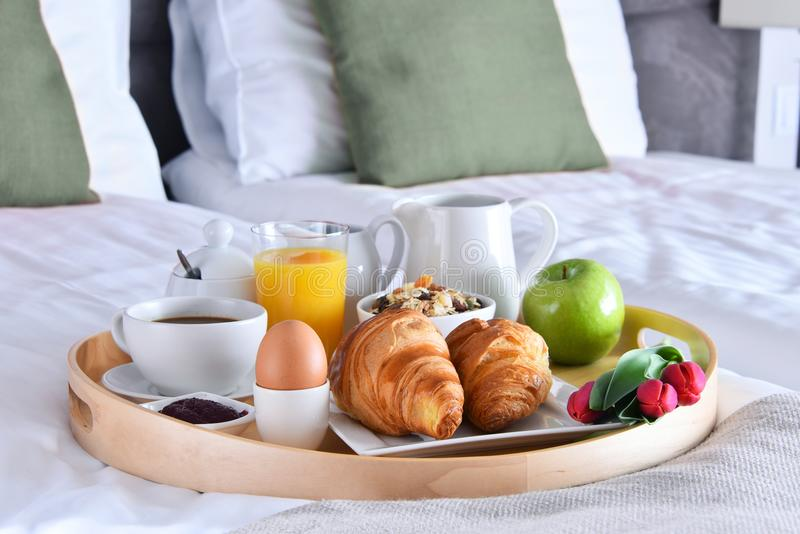 Breakfast on tray in bed in hotel room stock image