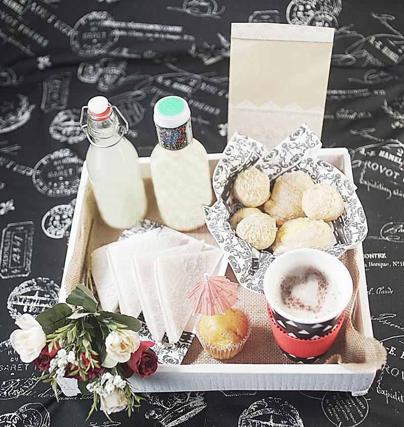 Breakfast tray with food and flowers. Breakfast tray on a bed with food and flowers on a bed royalty free stock photos