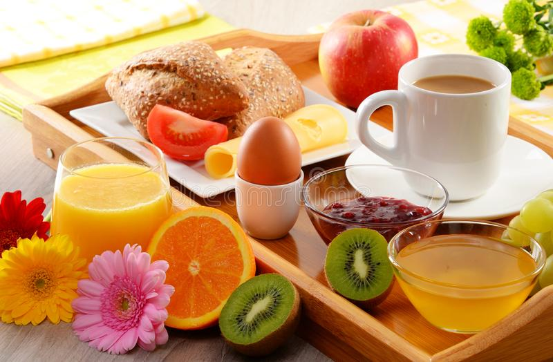 Breakfast on tray served with coffee, juice, egg, and rolls stock images