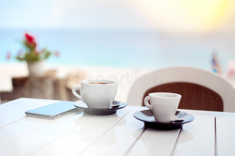 Breakfast for two in a cafe on the beach with two cups of coffee. And cell phone royalty free stock image