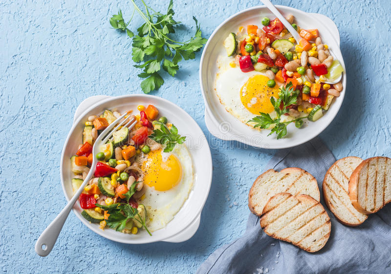 Breakfast vegetable hash with fried eggs on a blue background, top view. Healthy food. Concept stock images