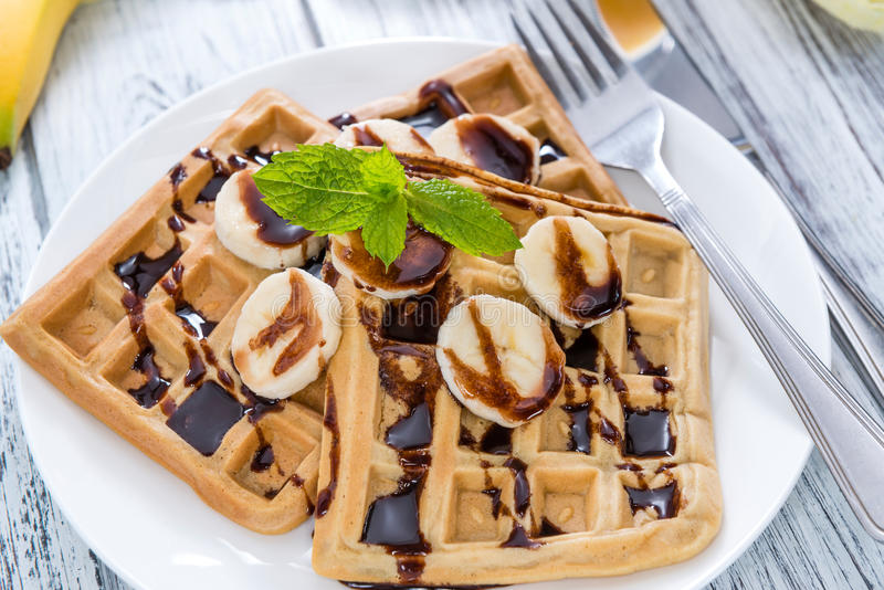 Breakfast (Waffles with Bananas and Chocolate Sauce). Breakfast table (Waffles with Bananas and Chocolate Sauce as close-up shot stock images