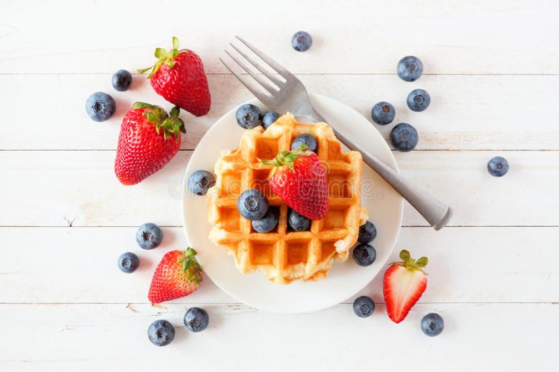 Breakfast waffles with strawberries and blueberries. Top view over white wood. Breakfast waffles with scattered strawberries and blueberries. Top view over a stock images