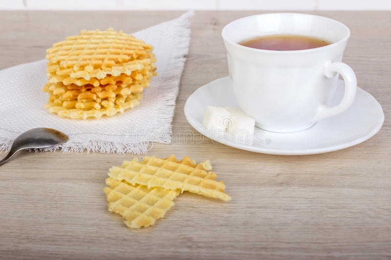 Breakfast with waffles stack on napkin and pieces of waffle with white cup of black tea on wooden surface.  stock photography
