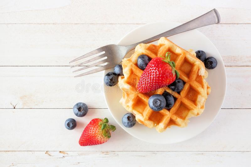 Breakfast waffles with strawberries and blueberries. Top view over white wood. Breakfast waffles with strawberries and blueberries. Top view over a white wood stock photography