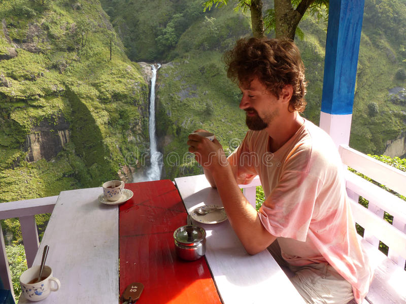 Breakfast with waterfall view - Chyamche village. Marsyangdi river valley - Annapurna Circuit trek in Nepal royalty free stock image