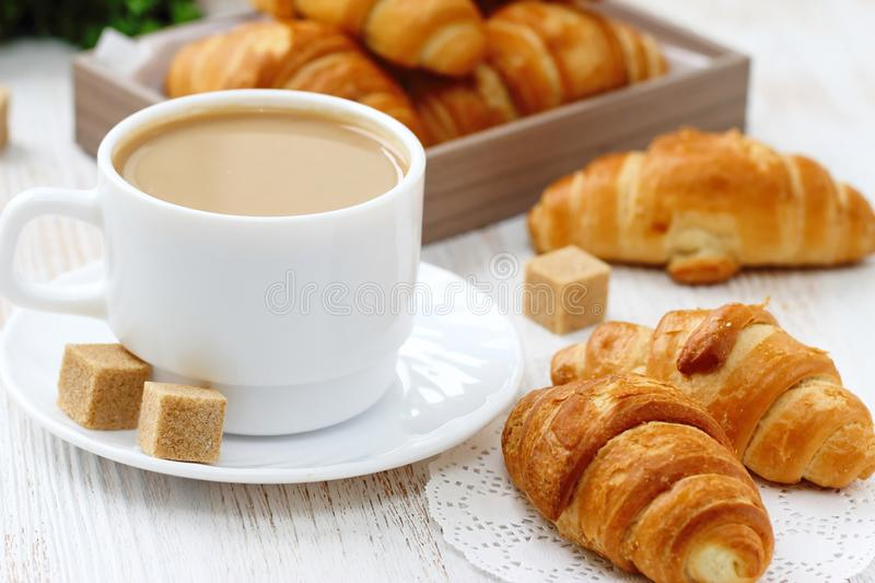 White coffee and croissant for breakfast. Breakfast with white coffee and sweet croissant with caramel royalty free stock images