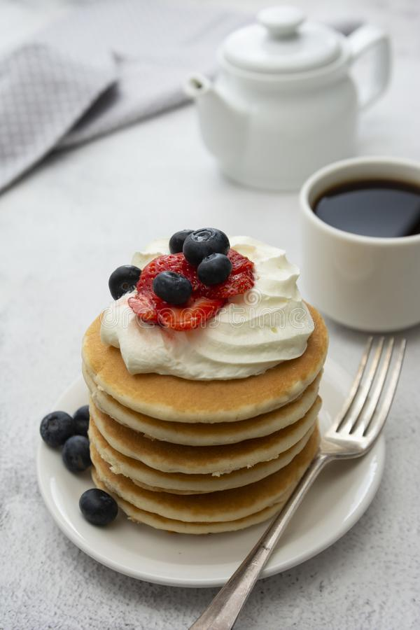 Breakfast wih Pancakes, cream, berry and coffee cup isolated on white background, copy space for text royalty free stock photo