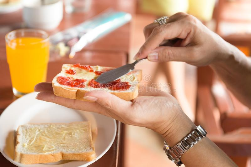 Breakfast with woman hand spreading strawberry jam on top slice stock photo