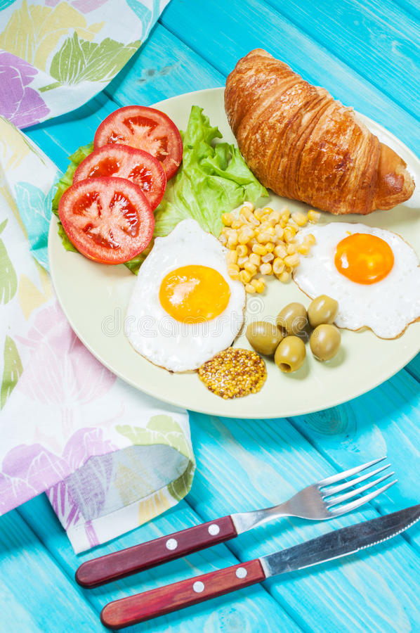 Breakfast on a wooden table. Fried eggs, tomatoes, croissant.  royalty free stock photos