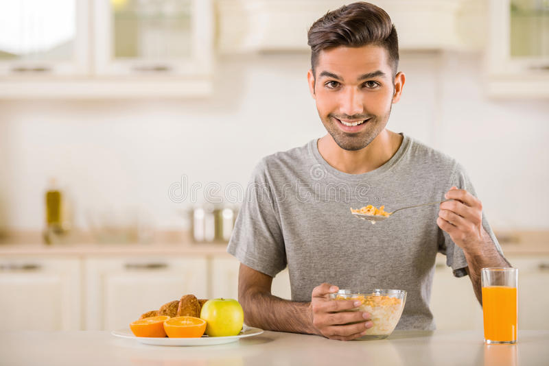 Breakfast. Young man in grey t-shirt eating corn flakes with milk and drinking juice for breakfast stock image