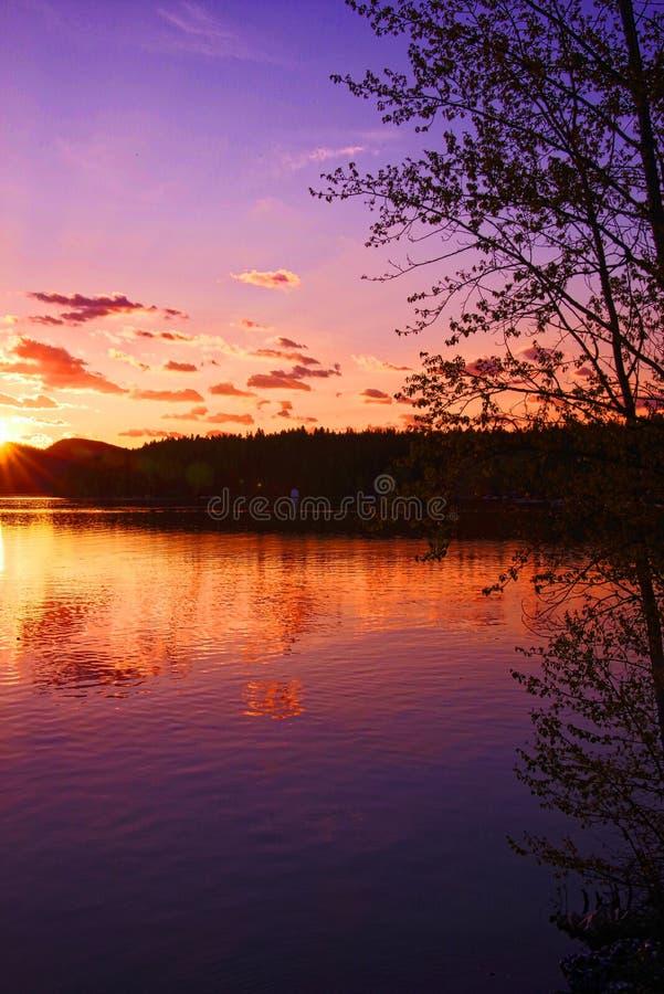 Whitefish Lake, Montana at dawn. Breaking dawn over banks of Whitefish Lake, Montana with pink and orange skies royalty free stock photos