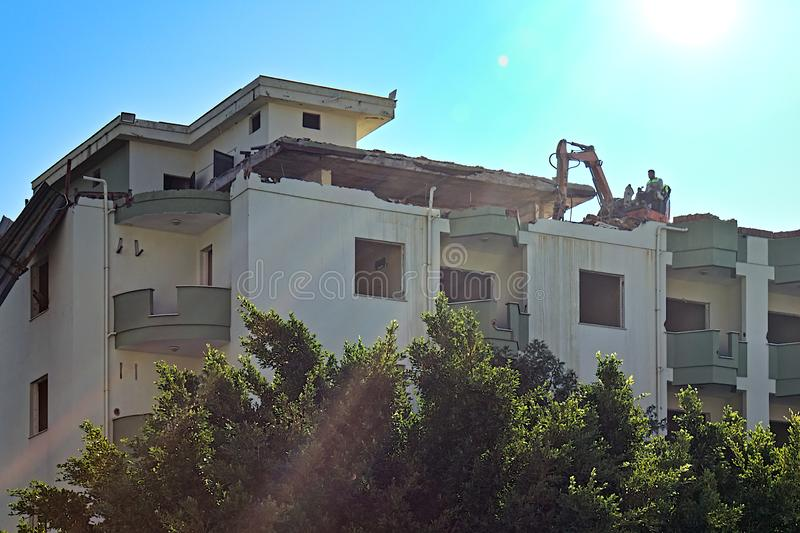 Breaking down an old apartment building, an excavator dismantles the building while on the top floor stock photography