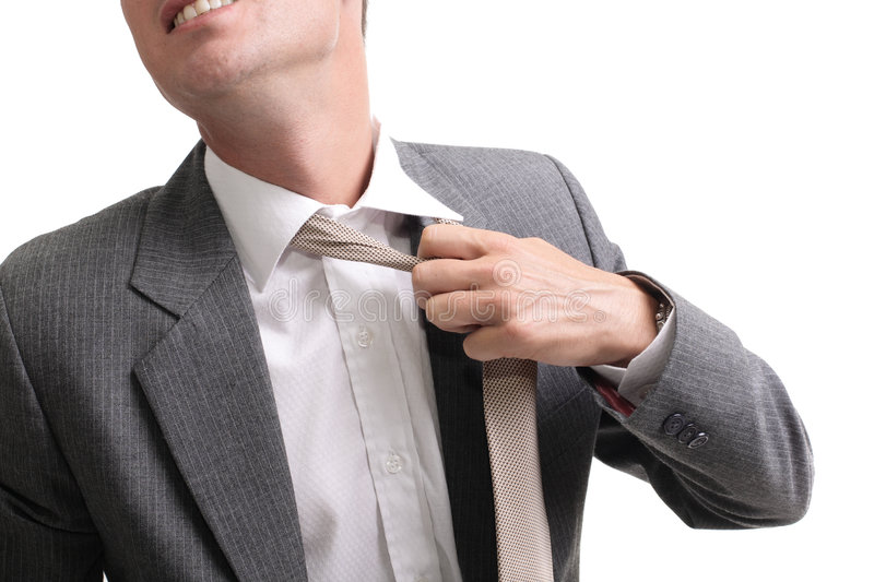 Breaking free!. Young stressed businessman unfastening his tie royalty free stock photos