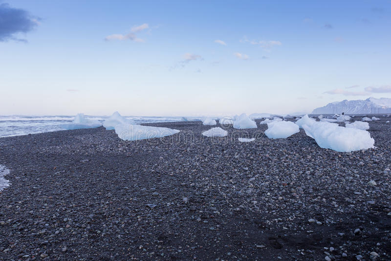 Breaking Ice from glacier on small black rock sand beach, Iceland stock images
