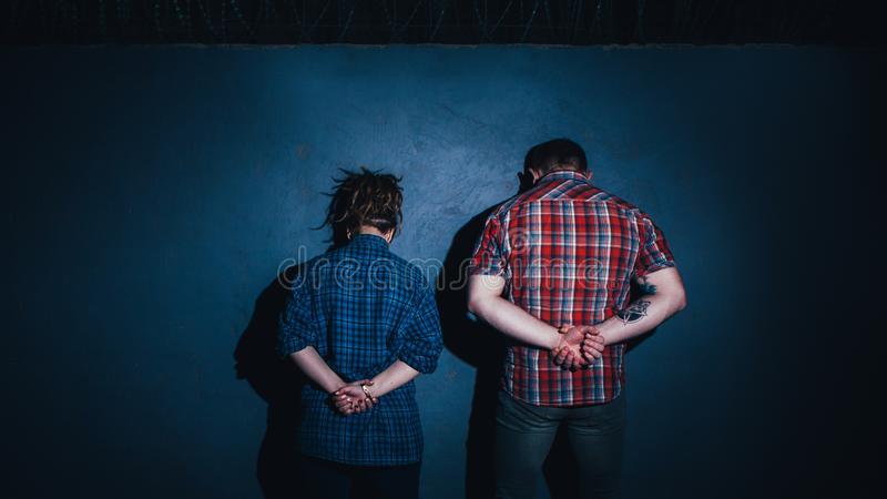 Breaking law illegal acts violation criminal. Breaking law. Illegal acts violation. Arrested criminal couple with hands behind back stock photos