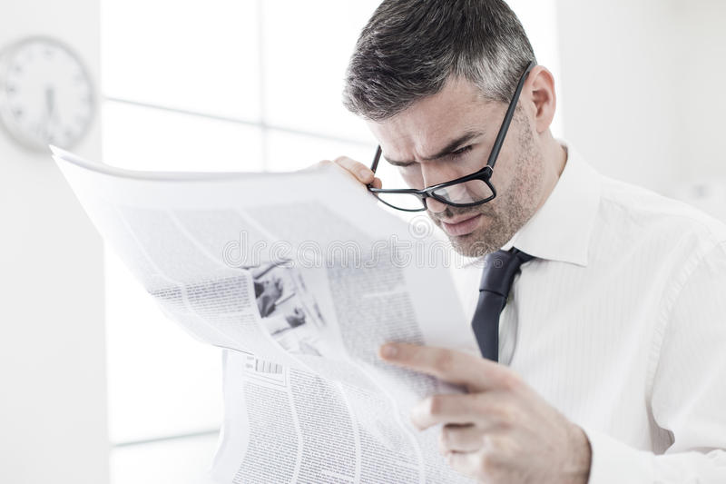 Breaking news. Businessman in the office, reading bad breaking news on a financial newspaper, he is shocked and adjusting his glasses stock photography